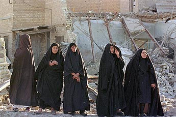 Five Iraqi women in black robes walking through a bomb-damaged street